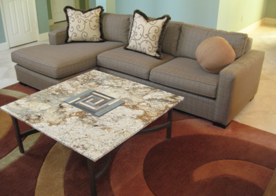 Custom coffee table with raised rectangular spiral inlaid into granite and a welded base
