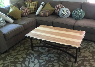 Custom sculpted and formed wood coffee table with a welded base