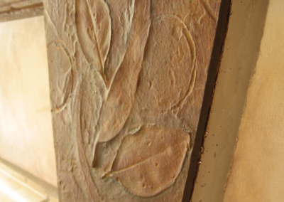 Detail of decorative leaf applique and rusted finish on fireplace keystone piece