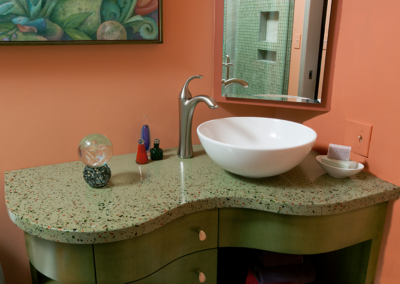 Custom cast concrete counter top with colored glass flecks and original cabinet design with custom mixed stain