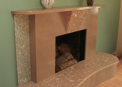 Custom designed cast concrete fireplace with embedded shell and abalone detailing